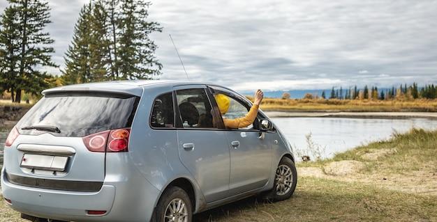 Mężczyzna w samochodzie obok rzeki i lasu, ciesząc się ciszą, słońcem i piękną jesienną przyrodą. koncepcja jesiennego nastroju