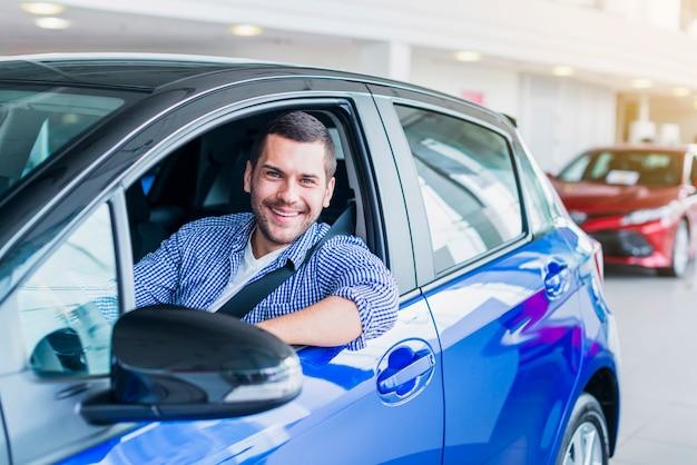 Mężczyzna w samochodzie przy przedstawicielstwem handlowym