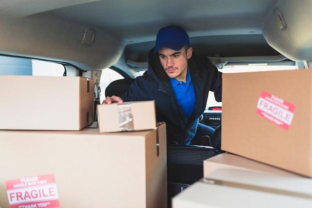 Mężczyzna w samochodzie sprawdza pudełka dla dostawy
