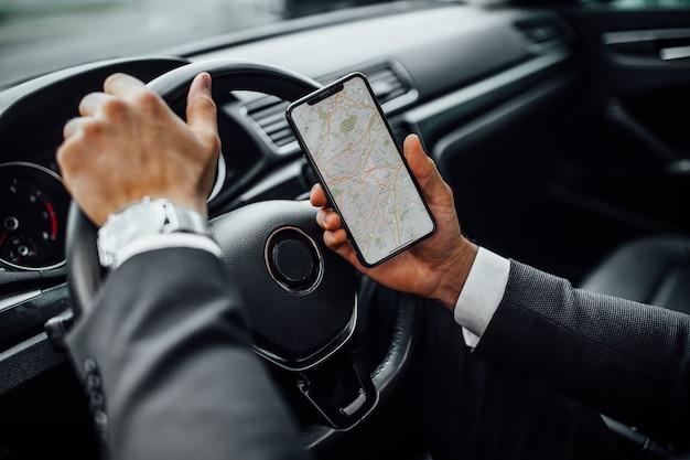 Mężczyzna w samochodzie trzymający smartfon z nawigacją po mapie gps