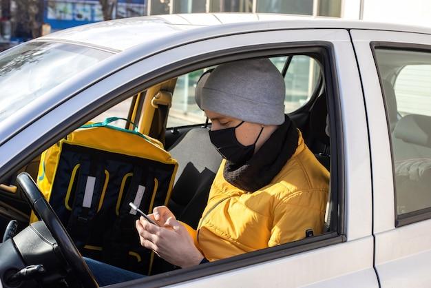 Mężczyzna w samochodzie w czarnej masce medycznej siedzi przy telefonie z plecakiem na siedzeniu