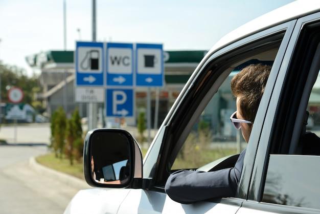 Mężczyzna w samochodzie zatrzymuje się na stacji benzynowej.