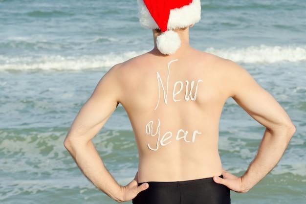 Mężczyzna w santa hat z napisem nowy rok na plecach stojący na plaży