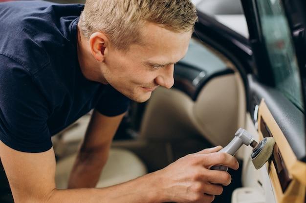 Mężczyzna w serwisie samochodowym poleruje detale samochodu