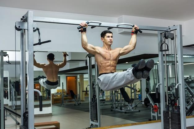 Mężczyzna w siłowni trenujący na poprzeczce, podnoszący się w górę