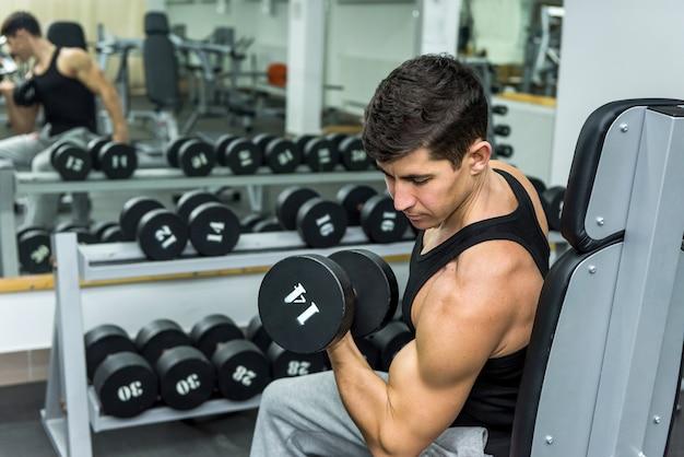 Mężczyzna w siłowni trzymający hantle z bliska