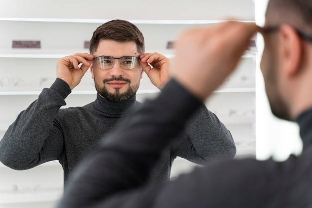 Mężczyzna w sklepie przymierza okulary