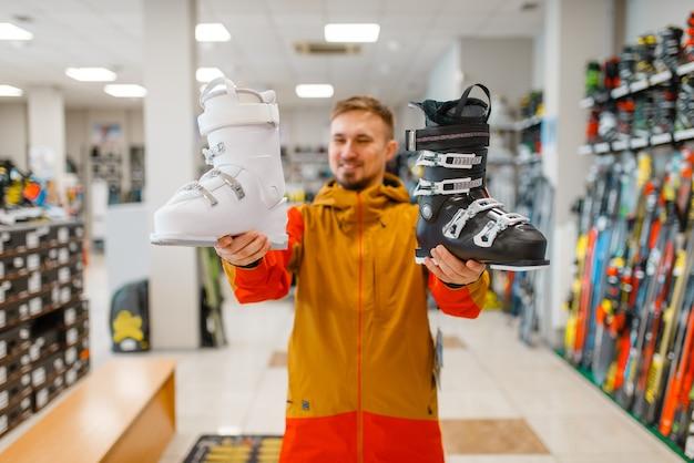 Mężczyzna w sklepie sportowym pokazuje biało-czarne buty narciarskie lub snowboardowe. sezon zimowy ekstremalny styl życia, aktywny wypoczynek, klient płci męskiej z wyposażeniem ochronnym