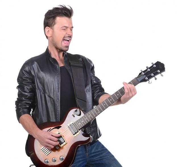 Mężczyzna w skórzanej kurtce gra na gitarze.