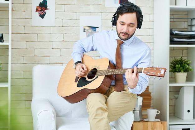 Mężczyzna w słuchawkach, gra na gitarze