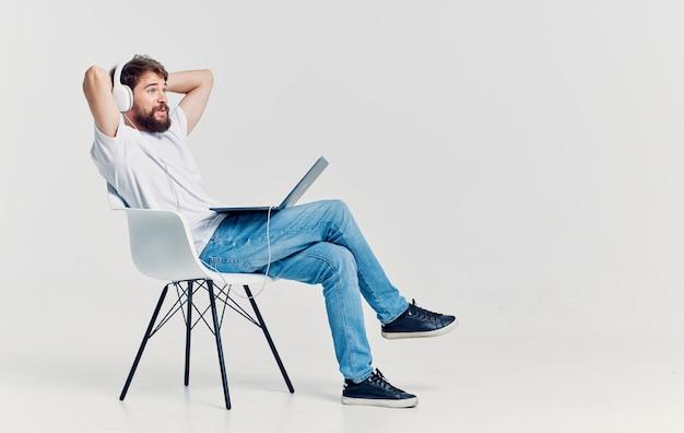 Mężczyzna w słuchawkach przed laptopem na krześle technologii rekreacji. wysokiej jakości zdjęcie