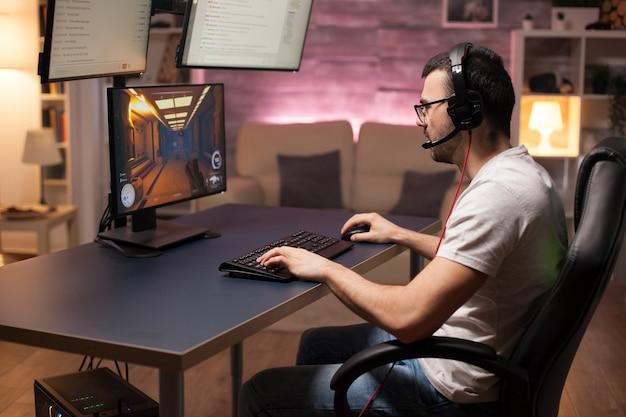 Mężczyzna w słuchawkach rozmawia ze swoim zespołem podczas grania w strzelanki online.