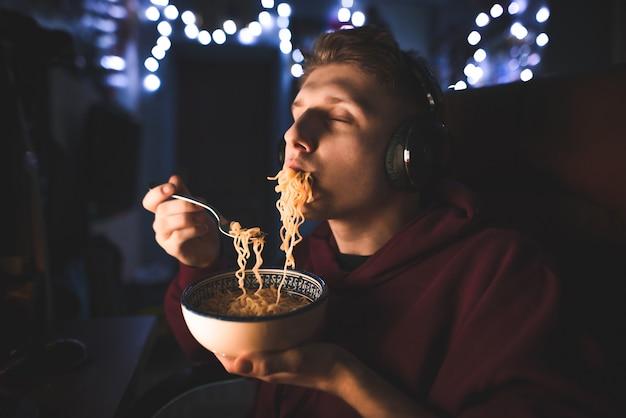 Mężczyzna w słuchawkach siedzi przy stole w pobliżu komputera i je nocną zupę z makaronem w pokoju