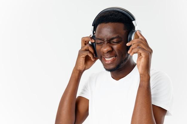 Mężczyzna w słuchawkach słucha muzyki emocje biała koszulka studio zabawy