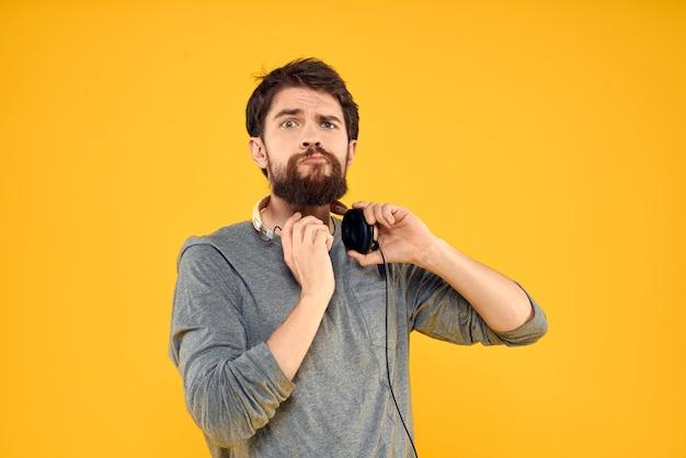 Mężczyzna w słuchawkach słucha technologii muzycznej na żółtym tle