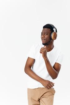 Mężczyzna w słuchawkach w białej koszulce słucha muzycznych emocji