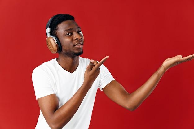 Mężczyzna w słuchawkach w białej koszulce słuchającej muzyki rozrywkowej na czerwonym tle
