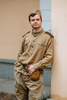 Mężczyzna w sowieckim mundurze z ii wojny światowej stoi przy żółtej ścianie
