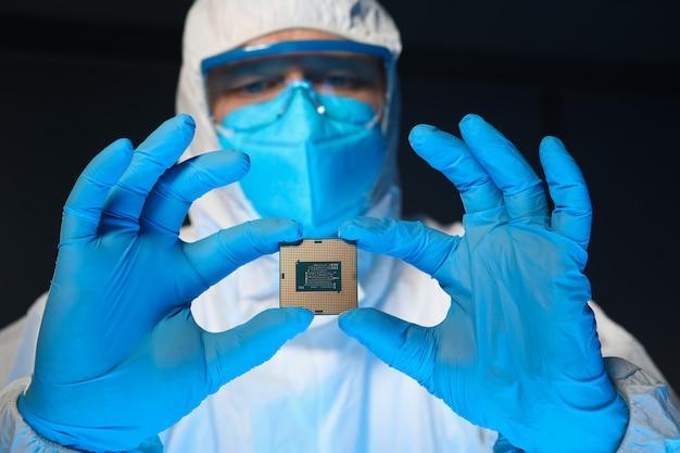 Mężczyzna w specjalnym mundurze pokazuje mikroprocesor
