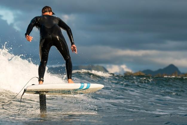 Mężczyzna w specjalnym sprzęcie surfuje na hawajach