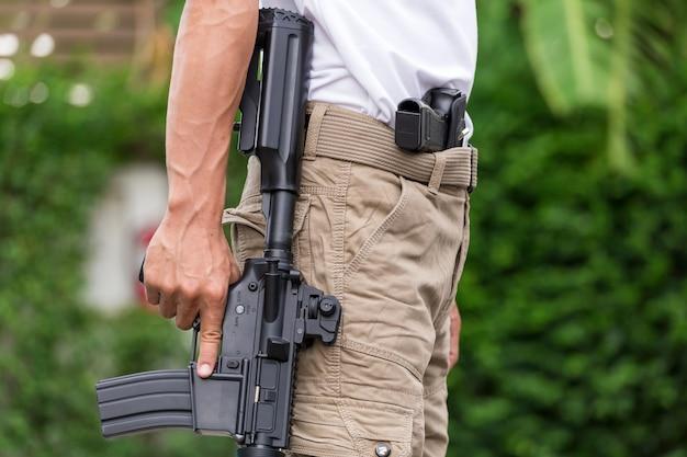 Mężczyzna w spodniach ładunkowych z pistoletem