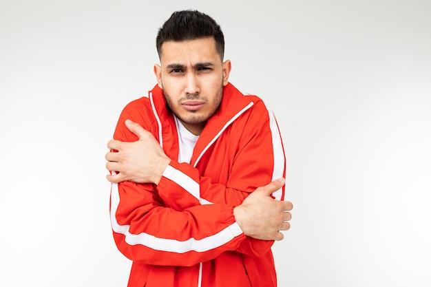 Mężczyzna w sportowym czerwonym garniturze przytula się, aby ogrzać się na białej przestrzeni kopii