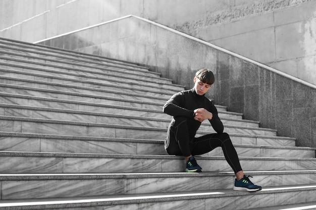Mężczyzna w sportowym stroju na schodach na zewnątrz