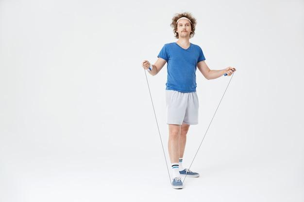 Mężczyzna w sportowym stroju retro, trzymając w ręku skakankę