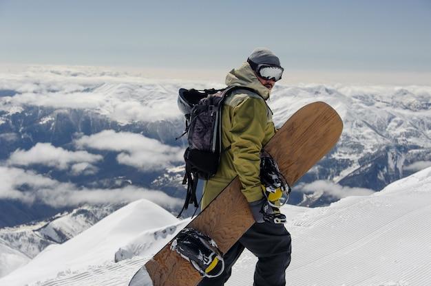 Mężczyzna w sprzęcie narciarskim, w okularach ochronnych, wznosi się na ośnieżoną górę na tle pochmurnego nieba