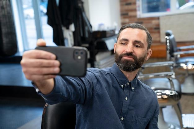 Mężczyzna w średnim ujęciu robi selfie