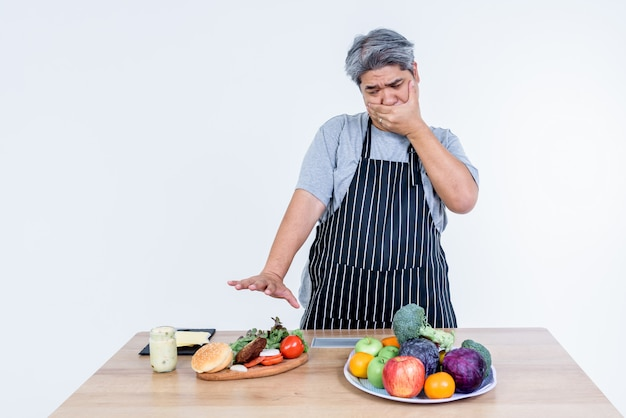 Mężczyzna w średnim wieku, azjatycki, zakrywa usta i odrzuca hamburgera