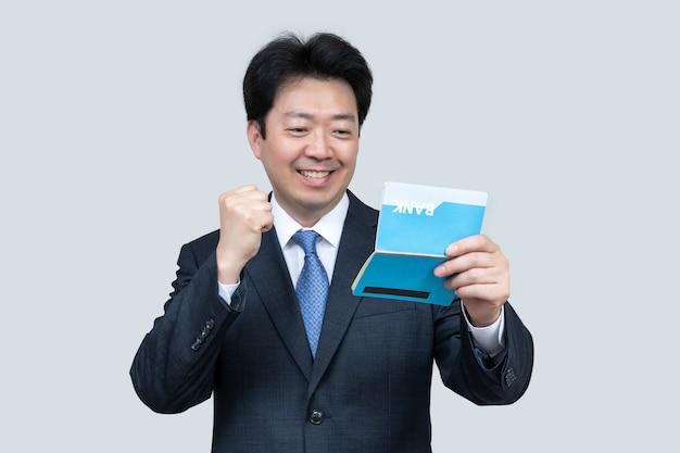 Mężczyzna w średnim wieku azji posiadający książeczkę bankową