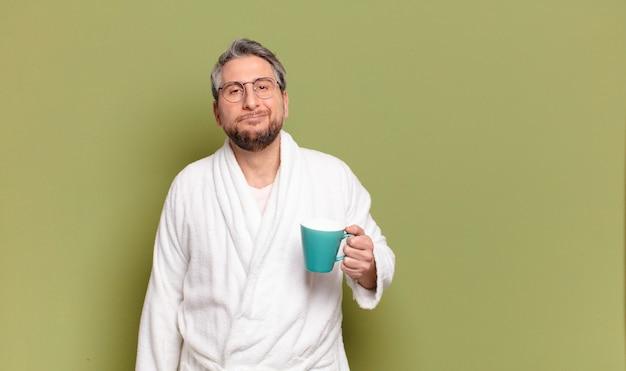 Mężczyzna w średnim wieku budzi się z filiżanką kawy