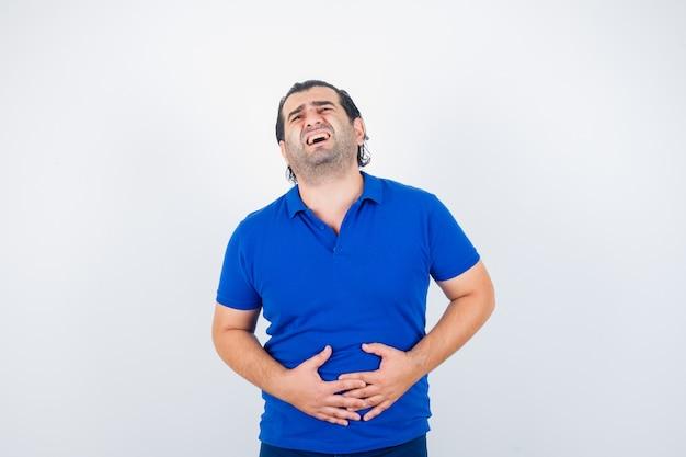 Mężczyzna w średnim wieku cierpiący na ból brzucha w niebieskiej koszulce i źle wyglądający. przedni widok.