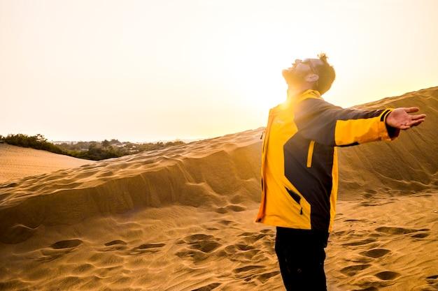 Mężczyzna w średnim wieku cieszący się wolnością i odkrywający sposób spędzania wolnego czasu, otwierając ramiona i przytulając się do natury. pustynne suche miejsce na alternatywny styl życia i czas wakacji. lato i zachód słońca
