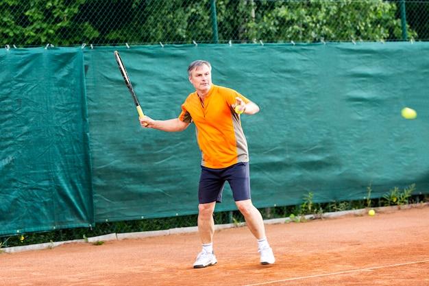 Mężczyzna w średnim wieku gra w tenisa na korcie o naturalnej powierzchni ziemi w słoneczny letni dzień.