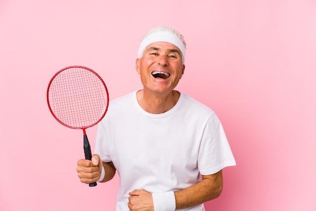 Mężczyzna w średnim wieku, grając w badmintona na białym tle, śmiejąc się i zabawy