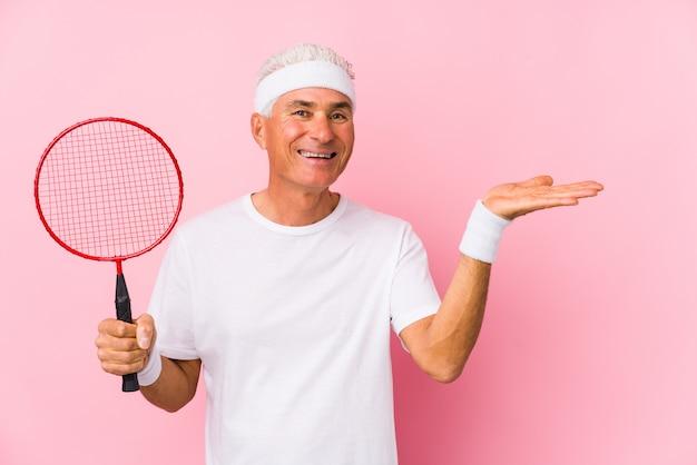 Mężczyzna w średnim wieku, grając w badmintona, pokazując kopię miejsca na dłoni i trzymając inną rękę na talii.