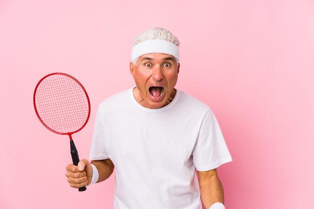 Mężczyzna w średnim wieku grający w badmintona krzyczy bardzo zły i agresywny.