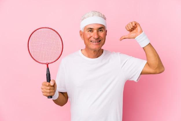 Mężczyzna w średnim wieku grający w badmintona na białym tle czuje się dumny i pewny siebie, przykład do naśladowania