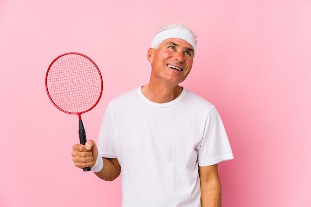 Mężczyzna w średnim wieku grający w badmintona na białym tle marzy o osiągnięciu celów