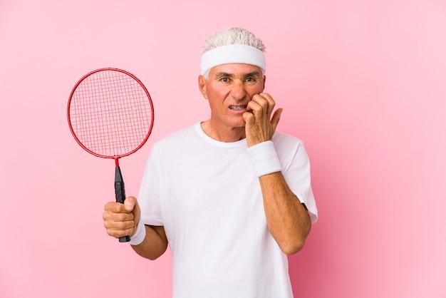 Mężczyzna w średnim wieku grający w badmintona na białym tle obgryzając paznokcie, nerwowy i bardzo niespokojny.