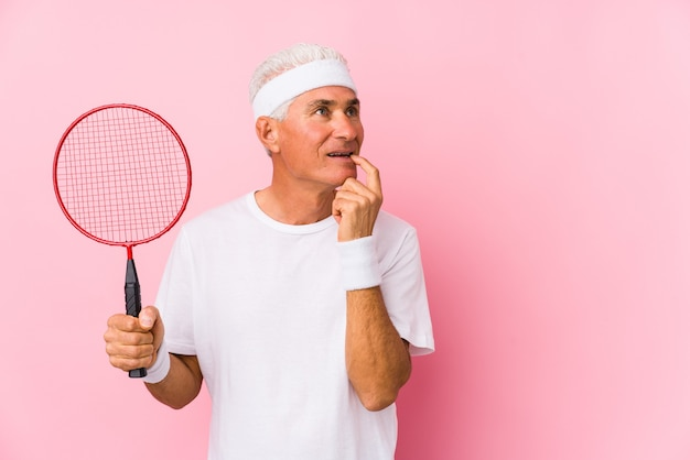 Mężczyzna w średnim wieku grający w badmintona na białym tle zrelaksowany myślenie o czymś, patrząc na przestrzeń kopii.