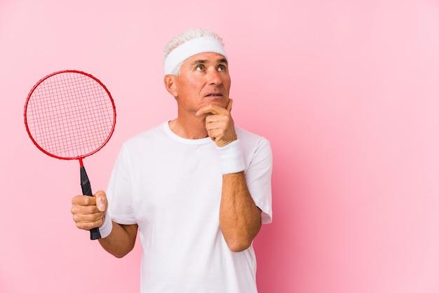Mężczyzna w średnim wieku, grający w badmintona, wyglądał na bok z wyrazem wątpliwości i sceptycyzmu.