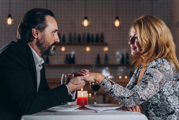 Mężczyzna w średnim wieku i kobieta jedzą posiłki w restauracji