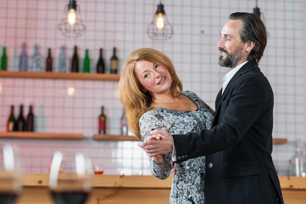 Mężczyzna w średnim wieku i kobieta tańczą w restauracji