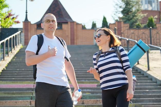 Mężczyzna w średnim wieku i kobieta w odzieży sportowej mówić chodzenia.