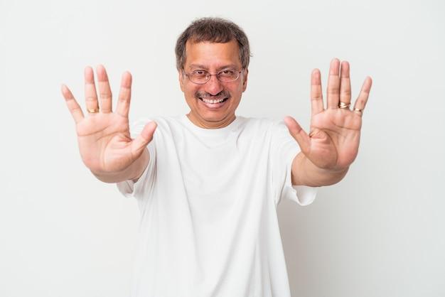Mężczyzna w średnim wieku indian na białym tle pokazując numer dziesięć z rękami.