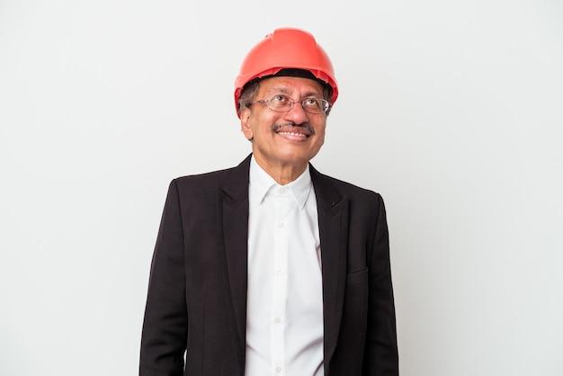Mężczyzna w średnim wieku indyjski architekt na białym tle marzy o osiągnięciu celów i celów