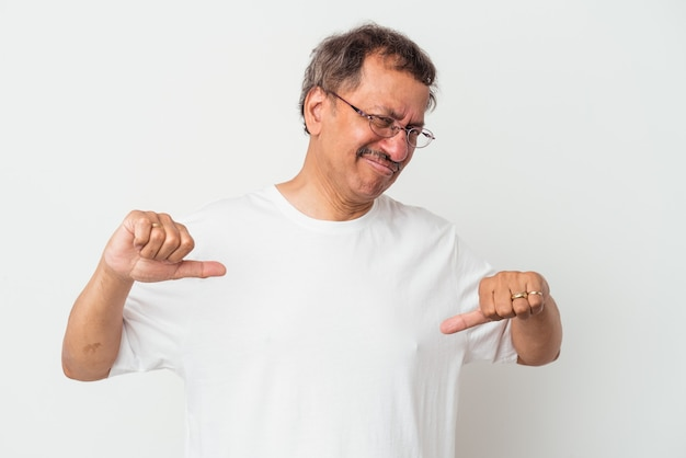 Mężczyzna w średnim wieku indyjski na białym tle pokazując kciuk w dół, koncepcja rozczarowanie.